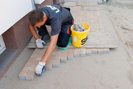 Процесс укладки тротуарной плитки специалистом